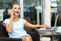 Young woman sitting in a cafe with a laptop and talking on the c Stock Photography