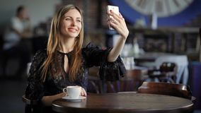 Young woman sitting in cafe and making selfie using modern smartphone. Lady in black sexy dress looking at the camera of stock footage