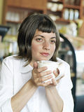 Young woman sitting at cafe table, holding mug of coffee, daydreaming, close-up Royalty Free Stock Photo