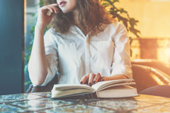 Young woman sitting in the cafe at the table with a paper book journal and looks thoughtfully out the window royalty free stock photography