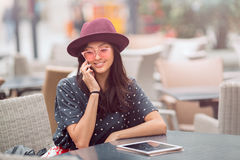 Young woman sitting at cafe and talk to the phone Royalty Free Stock Photography