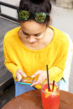 Young woman sitting at cafe using mobile phone Stock Photo