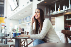 Young woman sitting in the cafeteria with laptop and using mobile phone Stock Photos