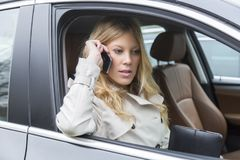 Young woman sitting in a car chatting on a mobile. Phone with a serious expression as she leans her elbow through the open window Stock Images