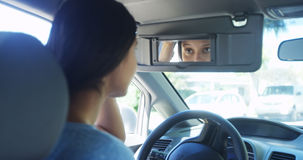 Young woman sitting in car checking her makeup in mirror Stock Image
