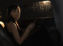 Young woman sitting in the car, on her phone, and looking at the camera on a rainy night in Beijing Stock Photography
