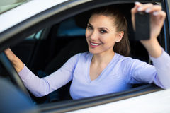 Young woman sitting in car holding car keys Royalty Free Stock Image