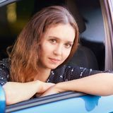 Young woman sitting in car. Ride instruction. Automobile loan stock image