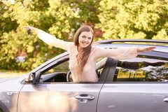 Young woman sitting in car. Ride instruction. Automobile loan royalty free stock photography