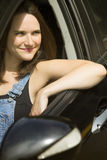 Young woman sitting in car and smiles Royalty Free Stock Photos