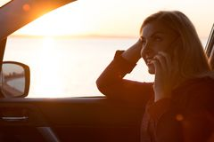 Young woman sitting in car and talking on the phone during sunset on the waterfront. royalty free stock photos