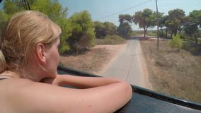 Young woman sitting in a car traveling along countryside road on sunny day vacation enjoying landscape -. Young woman sitting in a car traveling along stock video footage