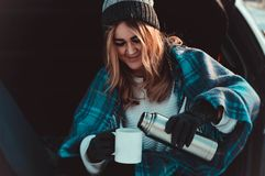 Young woman sitting on car trunk with coffee cups and thermos in winter field stock photos