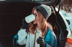 Young woman sitting on car trunk with coffee cups and thermos in winter field stock images