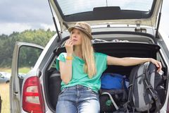 Young woman sitting in the car trunk with luggage. Summer road trip Stock Photography