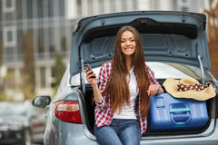 Young woman sitting in the car trunk with suitcases. Beautiful young brunette woman with long straight hair and brown eyes,a nice smile,the right hand wearing Stock Photo