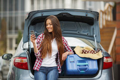 Young woman sitting in the car trunk with suitcases. Beautiful young brunette woman with long straight hair and brown eyes,a nice smile,the right hand wearing Stock Photos