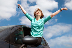 Young woman sitting on a car window and holding a key. Young girl sitting in the car and holding a key against blue sky Stock Photography