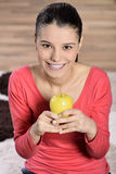Young woman sitting on carpet and enjoying apple Royalty Free Stock Photography