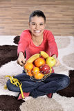 Young woman sitting on carpet and enjoying fruits Stock Photography