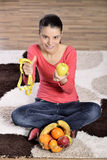 Young woman sitting on carpet and enjoying fruits Royalty Free Stock Photography