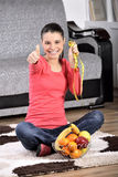 Young woman sitting on carpet and enjoying fruits Stock Photo