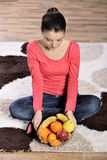 Young woman sitting on carpet and enjoying fruits Royalty Free Stock Images