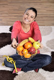 Young woman sitting on carpet and enjoying fruits Royalty Free Stock Photos