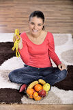 Young woman sitting on carpet and enjoying fruits Royalty Free Stock Photo