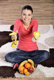 Young woman sitting on carpet and enjoying fruits Stock Images