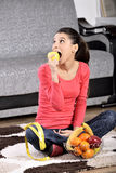 Young woman sitting on carpet and enjoying fruits Stock Photos