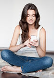 Young woman sitting with cell phone Royalty Free Stock Photo