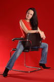 Young woman sitting on a chair Stock Photos