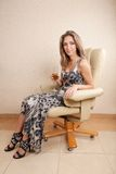 Young woman sitting in chair. Drinking champagne Royalty Free Stock Images