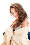 Young woman sitting on chair covered with blanket Royalty Free Stock Photography