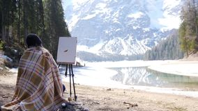 A young woman sitting on the chair covered in the plaid in Dolomites. Drawing a painting on nature. Mid shot stock footage