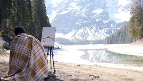 A young woman sitting on the chair covered in the plaid in Dolomites. Drawing a painting. Mid shot stock video footage