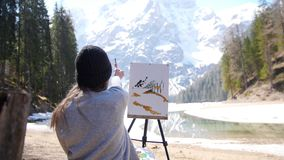 A young woman sitting on the chair in Dolomites. Drawing a painting on nature. Mid shot stock footage