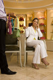 Young woman sitting on chair in glamorous boutique, male shop assistant showing her selection of designer handbags, woman using mo Stock Photos