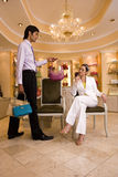Young woman sitting on chair in glamorous boutique, male shop assistant showing her selection of designer handbags Royalty Free Stock Image