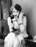 Young woman sitting on a chair holding a telephone Royalty Free Stock Photography