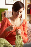 Young Woman Sitting In Chair Knitting Stock Photography