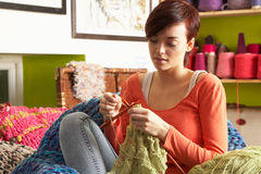 Young Woman Sitting In Chair Knitting. Concentrating royalty free stock image