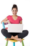 Young woman sitting on a chair with a laptop Royalty Free Stock Photos