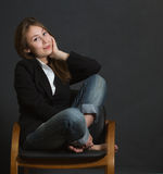 Young woman sitting chair legs crossed Stock Images