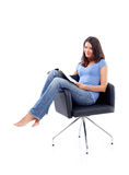 Young woman sitting in a chair with magazine Stock Image