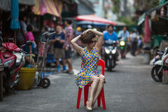 Young  woman is sitting on a chair in the middle of a bustling street. Royalty Free Stock Photos