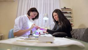 Young woman sitting in a chair in a nail salon, manicurist doing manicure client. A young woman sitting in a chair in a nail salon, manicurist doing manicure stock video footage