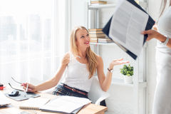 Young woman sitting on chair in office working and Royalty Free Stock Image