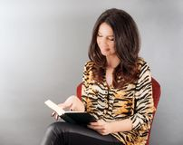 Woman sitting on a chair reading a book Stock Images